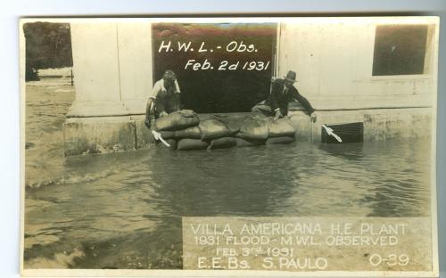 Os homens debruçados na janela indicam a altura atingida pela água durante a enchente.
