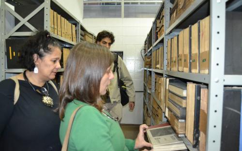 Equipe examinando documentos no arquivo climatizado